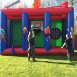 two boys throwing a basketball and a giant dart on the 3-in1 sports inflatable game