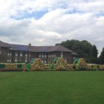 125ft army inflatable assault course inflated in a field in front of a block of flats