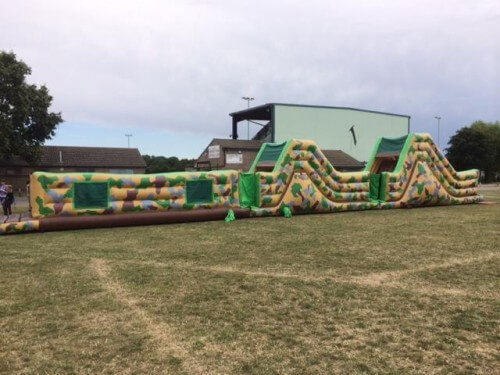 86ft inflatable army assault course in a field