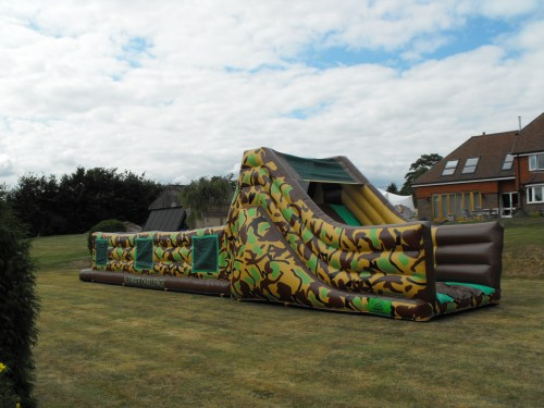 60ft army assault inflatable course in the backgarden of a house