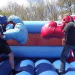 two boys geared up for a fight in a bouncy boxing inflatable with giant gloves and head guards