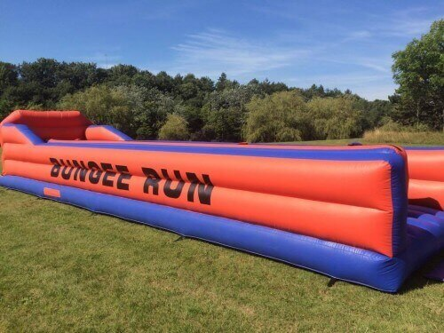 red and blue bungee run inflatable in a field