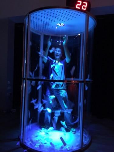 a man inside the LED lit cash grabber cube